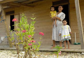 On the island of Nias, Indonesia, a family enjoys their new home which was reconstructed following the 2004 tsunami through the collaborative efforts of ACT Alliance partners. IOCC provided support for an integrated village recovery program on Nias Island