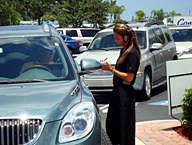 Waitress taking an order from waiting long line of cars