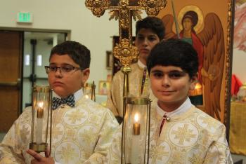 Altar servers process in front of an icon of the Archangel Michael at St. Michael Church in Van Nuys, CA.