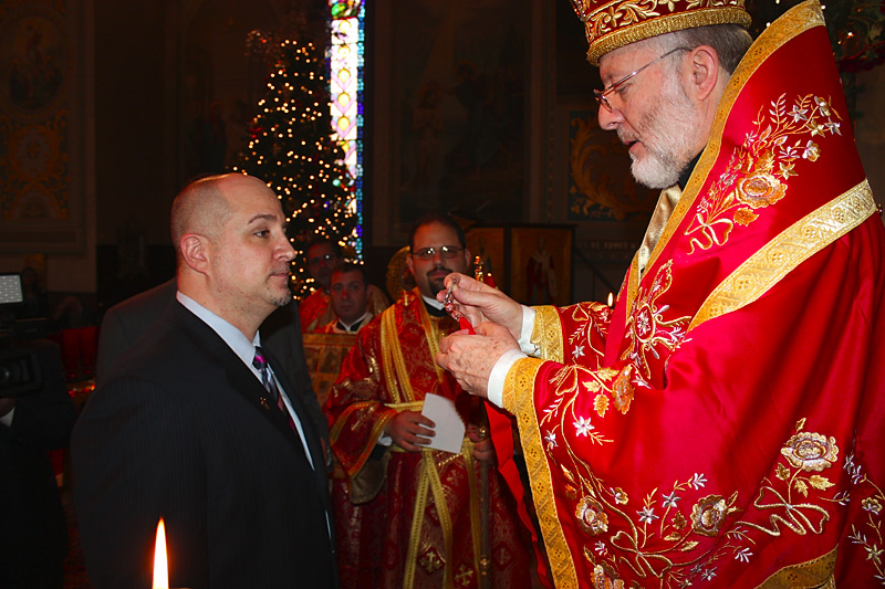 Bishop JOSEPH presenting the cross to Mark L. Simon