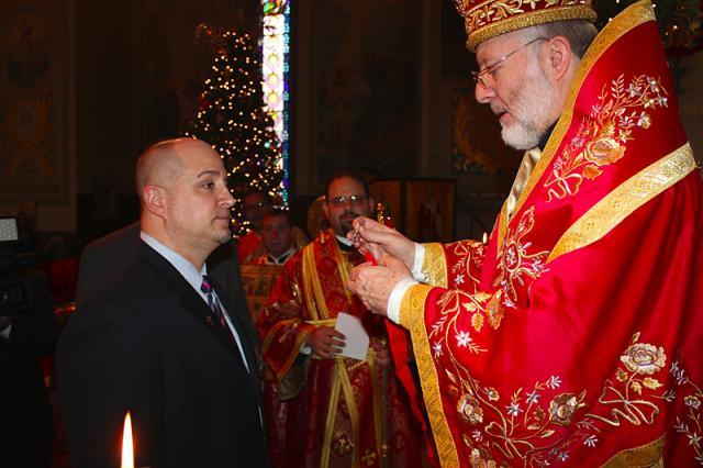 Bishop JOSEPH presenting the cross to Mark L. Simon