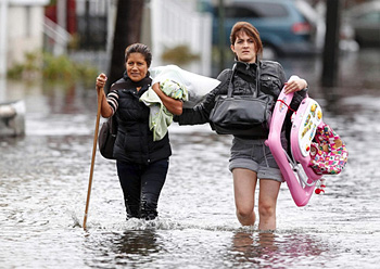 With an infant in arms, two East Coast residents slowly wade through knee-high flood waters brought on by Hurricane Sandy: IOCC Frontliners are responding to the disaster with trauma counseling for storm survivors, and assessing the emerging needs of families impacted by this expansive disaster. REUTERS/Adam Hunger