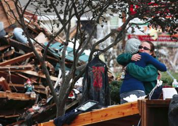 Two women embrace outside a home destroyed by storm surge flooding on hard-hit Staten Island in New York City following Hurricane Sandy. Through your generous support, IOCC is reaching out to storm survivors along the East Coast.