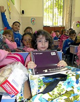 Iraqi refugees and disadvantaged Syrian children receive health and school kits at a public school in Syria. Many of the kits were assembled by Orthodox Christians and delivered by IOCC through its kit program. (Photo credit: IOCC Syria)