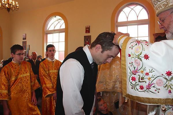 Jared Neufeldt receiving his Cross from His Grace Bishop Joseph