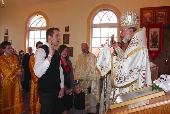 Jared Neufeldt being sworn in by Bishop Joseph with his sponsor Kim Franklin
