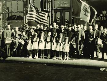 Al Hoda publishing company parade, in front of Al Hoda building. Photo source: Mary Mokarzel and The  University of Minnesota Immigration History Research Center