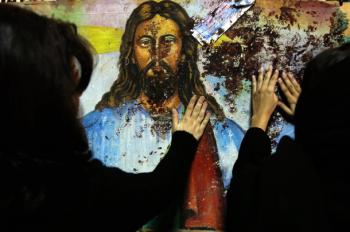 Egyptian Christians touch a blood-splattered image of Jesus Christ, inside the Coptic Orthodox church in Alexandria, January 2, 2011. REUTERS/Amr Abdallah Dalsh