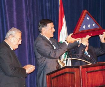 Congressman Darrell Issa (c.) awards the U.S. flag to Mr. Issam Fares (r.) as Metropolitan Philip (l.) looks on.