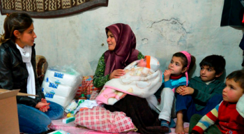 An IOCC nutritionist delivers supplies to a refugee mother (photo: Paul Jeffrey/IOCC)