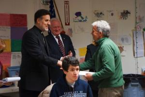 Fr. Tom Zain distributes gift card to Gerritson Beach resident