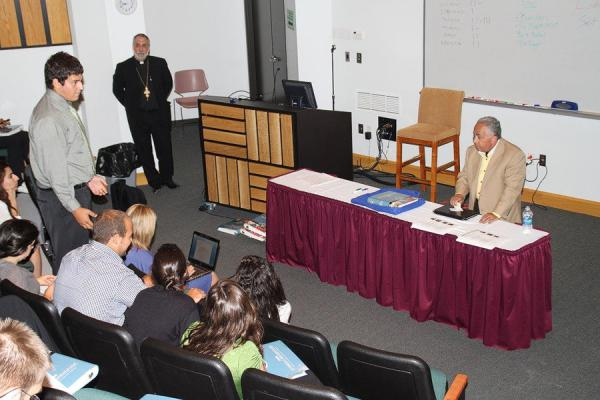 V. Rev. Fr. Joseph Purpura, Department of Youth Ministry Chair, looking on as Daniel Abraham answers questions from the teens of the Archdiocese.