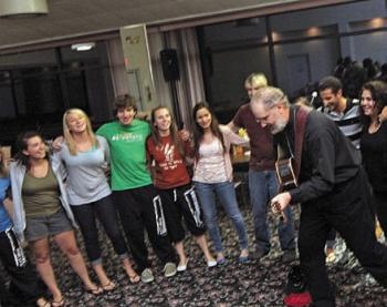 Fr. Patrick Kinder plays a guitar to entertain the teens on their last night