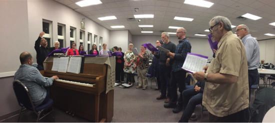 Director Nick AbouAssaly rehearses the choir during their Friday night workshop session with Paul advising from the piano.