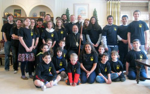 Kids and teens pose with their host, Bishop John, on Youth Day visit